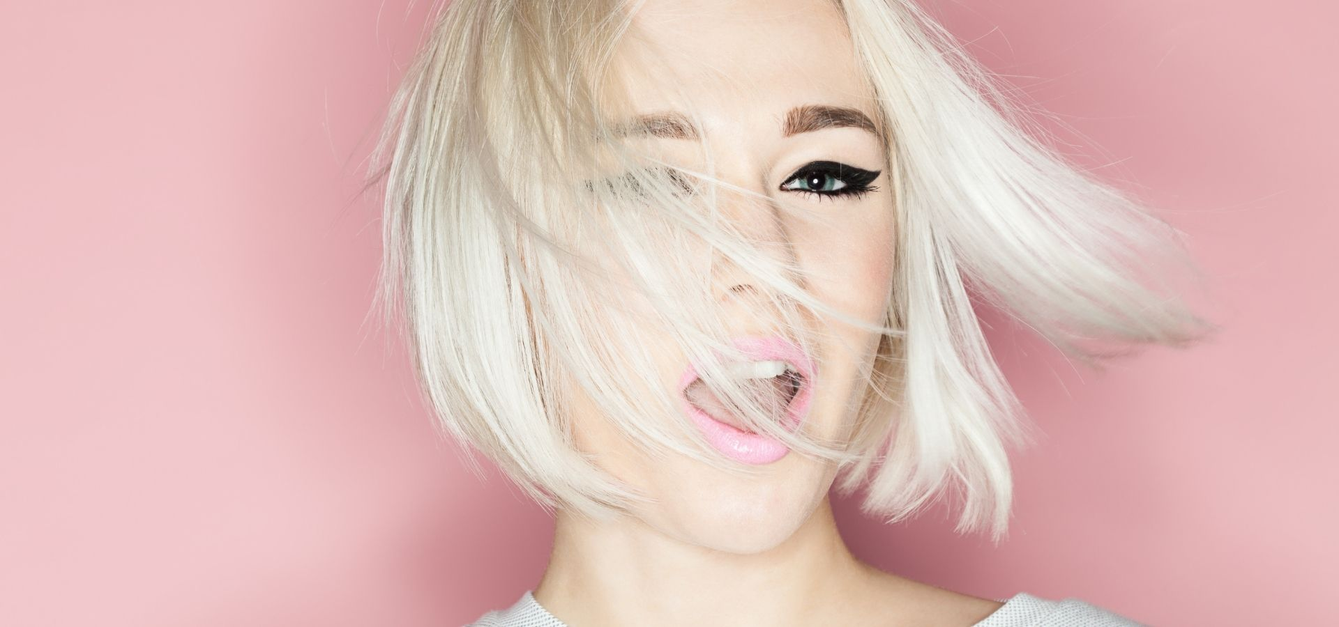 Fashion Blonde with stylish short white blonde hair infront of pink background