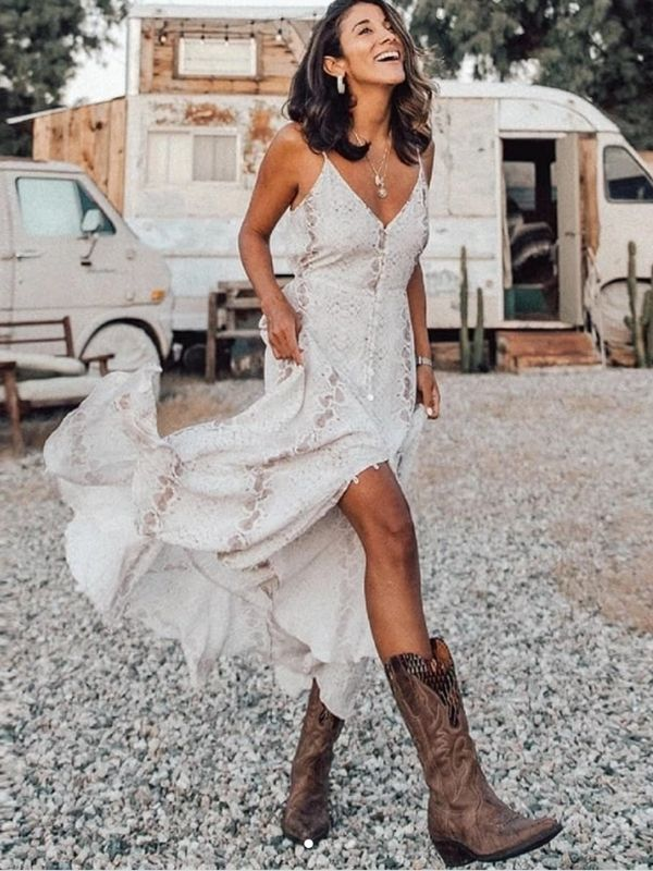 Laughing girl in a white maxi dress and boots