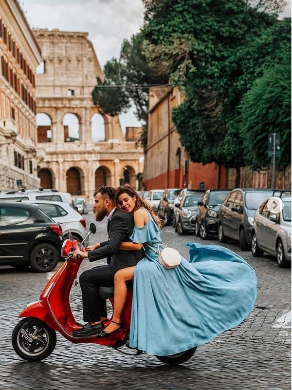 Couple on red scooter with the girl in a blue maxi dress