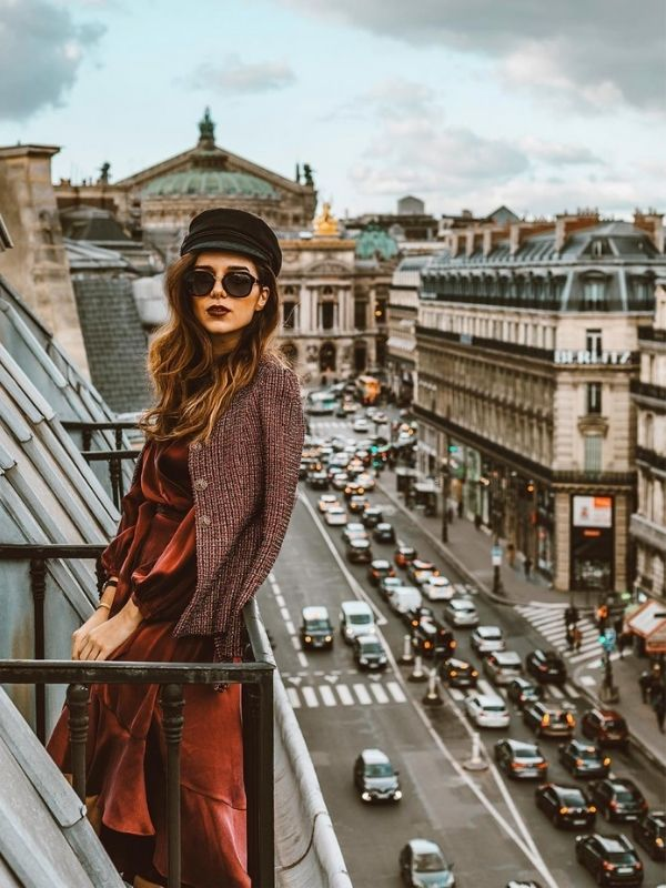 girl in a dark red maxi dress on a balcony