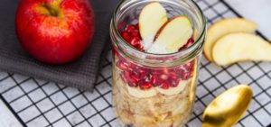Apple Pomegranate Overnight Oats_overnight oats in a glas jar with apple and pomegranate seeds on black baking tray with golden spoon