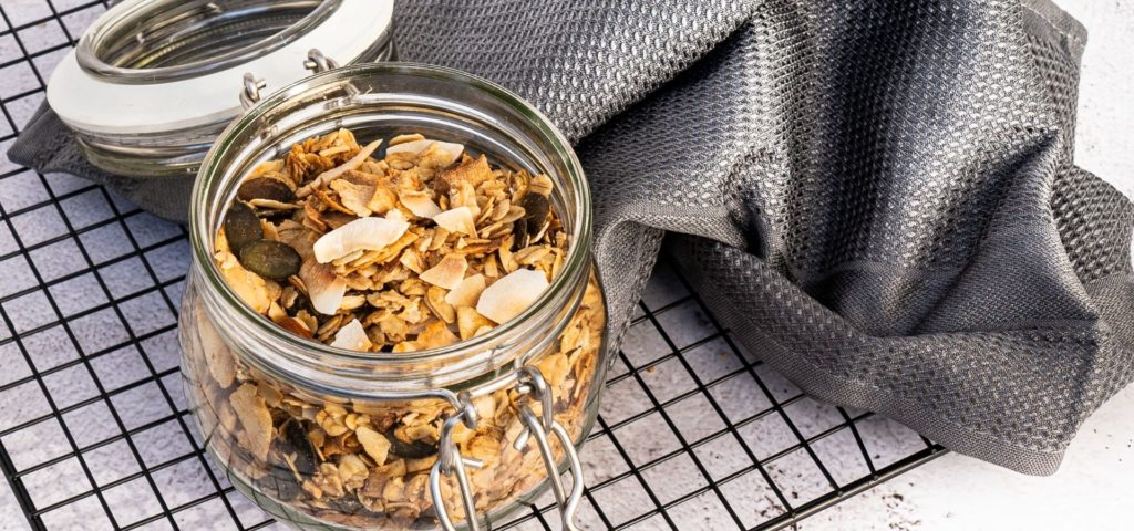 Coconut Granola_granola in a glas jar on a black baking tray