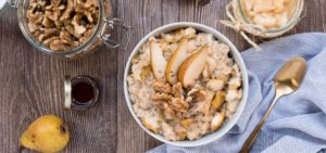 Flatlay of Porridge Bowl with golden Spoon , walnuts and pear puree