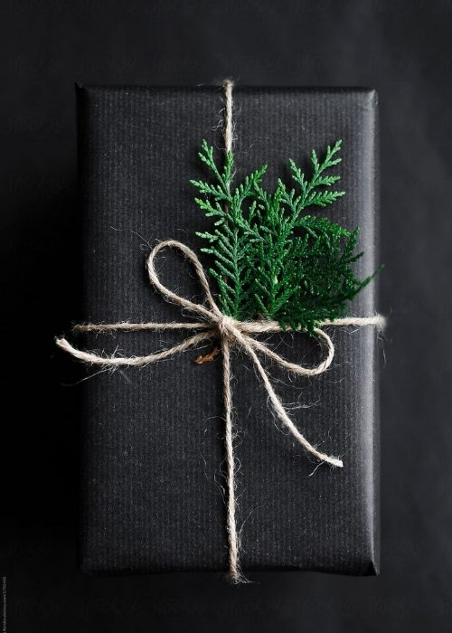 elegant and minimalist black christmas packaging with natural, rope and branch