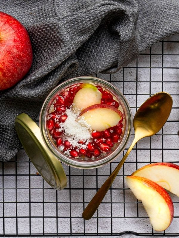 Apple Overnight Oats_overnight oats in a glas jar with apple and pomegranate seeds on black baking tray with golden spoon and apple_flatlay