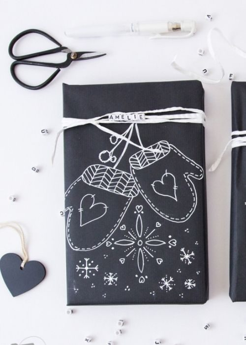 black christmas packaging with white writing and letter stones