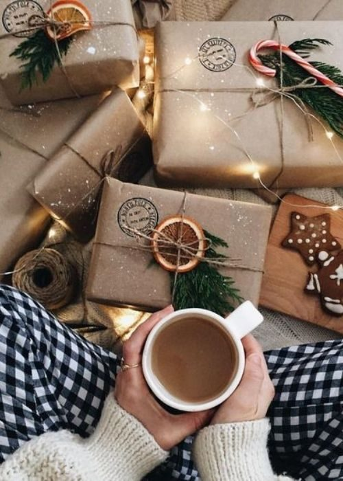 Girl with coffe cup sitting next to golden christmas packaging with greenery and oranges
