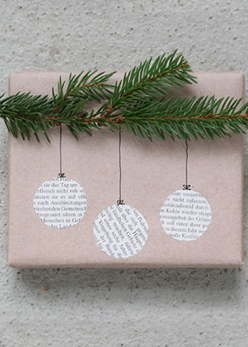beige rose christmas packaging with greenery and newspaper christmas balls