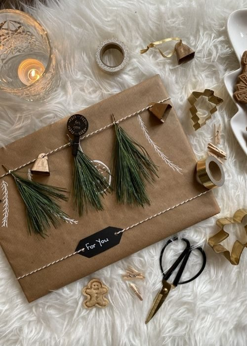 natural christmas packaging with greenery and golden ribbon